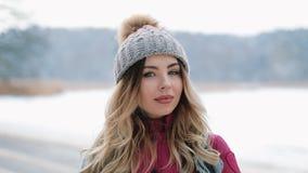 Η όμορφη γυναίκα στο χειμερινό καπέλο χαμογελά να σταθεί έξω στο χιόνι απόθεμα βίντεο