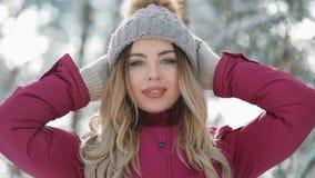 Η όμορφη γυναίκα στο χειμερινό καπέλο χαμογελά να σταθεί έξω στο χιόνι στο δασικό πορτρέτο όμορφη να εξετάσει κοριτσιών φιλμ μικρού μήκους