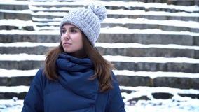 Η όμορφη γυναίκα στο χειμερινό καπέλο χαμογελά να σταθεί έξω στο χιόνι στο δάσος με το χιονώδες υπόβαθρο σκαλοπατιών Πορτρέτο του στοκ φωτογραφία