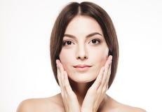 Η όμορφη γυναίκα σχετικά με τα μάγουλά της από τους φοίνικες κλείνει επάνω απομονωμένος στο λευκό στοκ φωτογραφίες