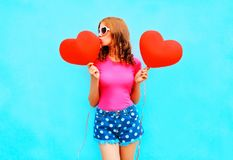 Η όμορφη γυναίκα φιλά ένα κόκκινο μπαλόνι με μορφή της καρδιάς στο μπλε Στοκ Φωτογραφία