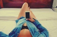 Η όμορφη γυναίκα φορά ένα πουκάμισο τζιν και κρατά ένα τηλέφωνο στο χέρι της στοκ φωτογραφία