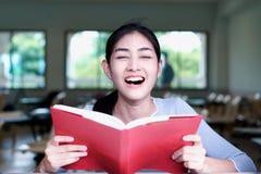 Η όμορφη γυναίκα χαμογελά και διαβάζει ένα βιβλίο από το παράθυρο στο cla στοκ εικόνες με δικαίωμα ελεύθερης χρήσης