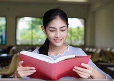 Η όμορφη γυναίκα χαμογελά και διαβάζει ένα βιβλίο από το παράθυρο στο cla στοκ φωτογραφίες με δικαίωμα ελεύθερης χρήσης