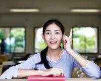 Η όμορφη γυναίκα χαμογελά και διαβάζει ένα βιβλίο από το παράθυρο στο cla στοκ φωτογραφία με δικαίωμα ελεύθερης χρήσης