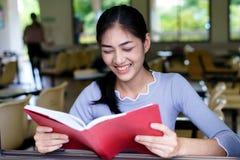 Η όμορφη γυναίκα χαμογελά και διαβάζει ένα βιβλίο από το παράθυρο στο cla στοκ εικόνα με δικαίωμα ελεύθερης χρήσης