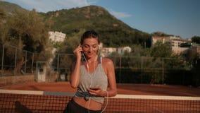 Η όμορφη γυναίκα χορεύει με τα ακουστικά σε ένα γήπεδο αντισφαίρισης το καλοκαίρι απόθεμα βίντεο