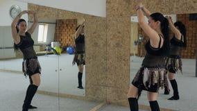 Η όμορφη γυναίκα χορεύει χορός κοιλιών στο στούντιο με πολλούς καθρέφτες απόθεμα βίντεο