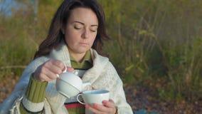 Η όμορφη γυναίκα χύνει το τσάι από teapot πορσελάνης που τυλίγεται στο καρό στην αυγή απόθεμα βίντεο