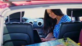 Η όμορφη γυναίκα brunette σε ένα μπλε φόρεμα, κάθεται στο αυτοκίνητο, εργάζεται στο lap-top, επικοινωνώντας στα κοινωνικά δίκτυα  απόθεμα βίντεο