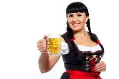 Η όμορφη γυναίκα brunette σε βαυαρικό έντυσε με το ποτήρι της μπύρας Στοκ Φωτογραφία