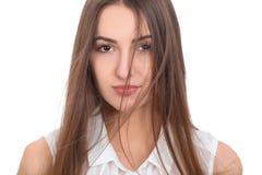 Η όμορφη γυναίκα brunette σε μια άσπρη μπλούζα και έναν ελαφρύ αέρα φύσηξε την τρίχα της Απομονωμένο υπόβαθρο στοκ φωτογραφία