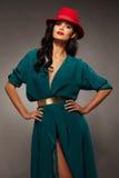 Η όμορφη γυναίκα brunette στο κόκκινο καπέλο με το κόκκινο κραγιόν και το τυρκουάζ βράδυ ντύνουν με τη ζώνη Στοκ Φωτογραφίες