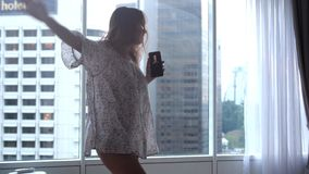Η όμορφη γυναίκα brunette χορεύει κοντά στα πανοραμικά παράθυρα απολαμβάνοντας τη μουσική με το κινητό τηλέφωνο στο διαμέρισμα με απόθεμα βίντεο