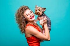 Η όμορφη γυναίκα ` s στα κόκκινα dresss με το σκυλί τεριέ του Γιορκσάιρ δίνει τα φιλιά που απομονώνονται στο υπόβαθρο χρώματος στοκ φωτογραφίες με δικαίωμα ελεύθερης χρήσης