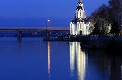 Η όμορφη εκκλησία με τη διαφώτιση στη νύχτα φθινοπώρου, φω'τα απεικόνισε στον ποταμό Dnieper Στοκ Εικόνα