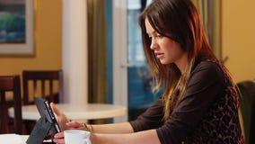 Η όμορφη ελκυστική νέα γυναίκα διαβάζει τις ειδήσεις στο γραφείο PC ταμπλετών φιλμ μικρού μήκους