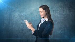 Η όμορφη επιχειρηματίας εξετάζει ένα μαξιλάρι αφής και χαμογελά, μπλε υπόβαθρο Στοκ Εικόνα
