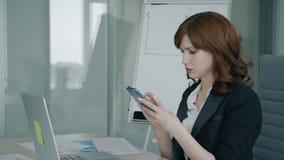 Η όμορφη επιχειρηματίας χρησιμοποιεί την τηλεφωνική συνεδρίαση στον πίνακα στην επιχείρηση απόθεμα βίντεο