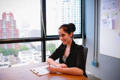 Η όμορφη επιχειρησιακή γυναίκα κάθεται και γράφει το επιχειρηματικό σχέδιο σε χαρτί στοκ φωτογραφίες