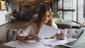 Η όμορφη επιχειρησιακή γυναίκα υπογράφει τα έγγραφα και το άκουσμα στη μουσική στα ακουστικά απόθεμα βίντεο