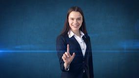Η όμορφη επιχειρησιακή γυναίκα ωθεί ένα αόρατο κουμπί, γκρίζο υπόβαθρο Στοκ φωτογραφία με δικαίωμα ελεύθερης χρήσης
