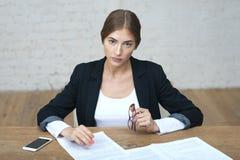 Η όμορφη επιχειρησιακή κυρία κοιτάζει επίμονα στους υπαλλήλους στη συνεδρίαση Στοκ Φωτογραφία