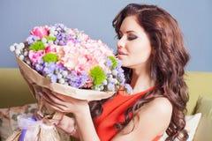 Η όμορφη ευτυχής γυναίκα έλαβε μια ανθοδέσμη λουλουδιών των τριαντάφυλλων Στοκ Φωτογραφίες