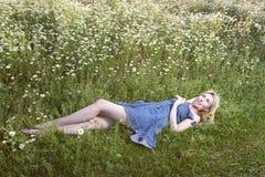 Η όμορφη ευτυχής νέα γυναίκα βρίσκεται στον τομέα των chamomiles Στοκ Εικόνες