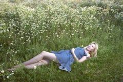 Η όμορφη ευτυχής νέα γυναίκα βρίσκεται στον τομέα των chamomiles Στοκ εικόνα με δικαίωμα ελεύθερης χρήσης