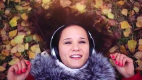 Η όμορφη ευτυχής νέα γυναίκα με τα ακουστικά που βρίσκονται στο φθινόπωρο αφήνει το άκουσμα στη μουσική απόθεμα βίντεο