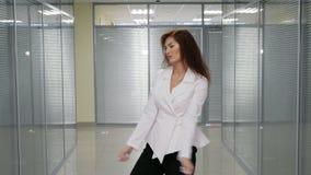 Η όμορφη ευτυχής νέα επιχειρησιακή γυναίκα χόρεψε στο γραφείο hallwall φιλμ μικρού μήκους