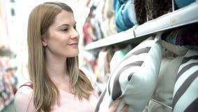 Η όμορφη ελκυστική νέα γυναίκα επιλέγει τα μαξιλάρια στα ράφια στο κατάστημα Έννοια καταναλωτισμού απόθεμα βίντεο
