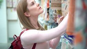 Η όμορφη ελκυστική νέα γυναίκα επιλέγει τα τραπεζομάντιλα στα ράφια στο κατάστημα Έννοια καταναλωτισμού απόθεμα βίντεο