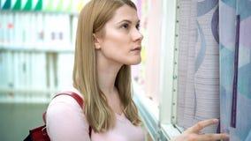 Η όμορφη ελκυστική νέα γυναίκα επιλέγει την ταπετσαρία στα ράφια στο κατάστημα Έννοια καταναλωτισμού απόθεμα βίντεο