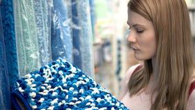 Η όμορφη ελκυστική νέα γυναίκα επιλέγει τις κουβέρτες στα ράφια στο κατάστημα Έννοια καταναλωτισμού φιλμ μικρού μήκους