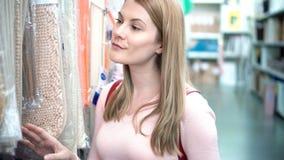 Η όμορφη ελκυστική νέα γυναίκα επιλέγει τις κουβέρτες στα ράφια στο κατάστημα Έννοια καταναλωτισμού απόθεμα βίντεο
