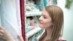 Η όμορφη ελκυστική νέα γυναίκα επιλέγει τους τυφλούς στα ράφια στο κατάστημα Έννοια καταναλωτισμού απόθεμα βίντεο