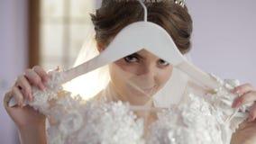Η όμορφη και καλή νύφη στην εσθήτα νύχτας κρατά την κρεμάστρα με ένα γαμήλιο φόρεμα Γαμήλιο πρωί Αρκετά και καλά-καλλωπισμένη γυν απόθεμα βίντεο