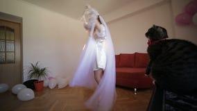 Η όμορφη και καλή νύφη στην εσθήτα νύχτας κρατά την κρεμάστρα με ένα γαμήλιο φόρεμα και το χορό με αυτό το φόρεμα Η γάτα κάθεται  απόθεμα βίντεο