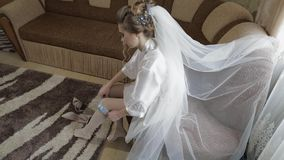Η όμορφη και καλή νύφη στην εσθήτα νύχτας φορά γαμήλιο garter στο πόδι της απόθεμα βίντεο