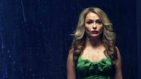 Η όμορφη και νέα γυναίκα στο πράσινο φόρεμα που στέκεται μπροστά από το παράθυρο και που κοιτάζει στη βροχή μειώνεται φιλμ μικρού μήκους