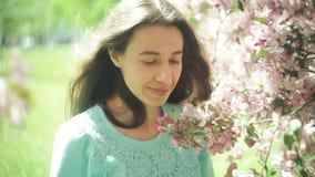 Η όμορφη καλή και νέα γυναίκα στα λουλούδια του δέντρου διακλαδίζεται την άνοιξη απόθεμα βίντεο