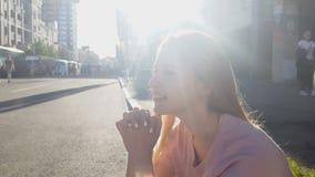 Η όμορφη καλή συνεδρίαση κοριτσιών στο πεζοδρόμιο, η ονειροπόλος κυρία, ξένοιαστο μέλλον απόθεμα βίντεο