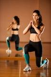Η όμορφη κατάλληλη γυναίκα επιλύει σε μια γυμναστική ικανότητας που κάνει lunge το βήμα Στοκ εικόνα με δικαίωμα ελεύθερης χρήσης