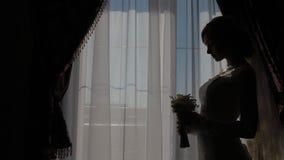 Η όμορφη καυκάσια νύφη θέτει κοντά στο παράθυρο απόθεμα βίντεο
