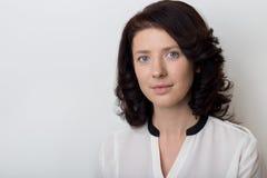 Η όμορφη κομψή γυναίκα καταδεικνύει την εφαρμογή του makeup σε ένα άσπρο υπόβαθρο στο στούντιο Στοκ Εικόνα