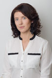 Η όμορφη κομψή γυναίκα καταδεικνύει την εφαρμογή του makeup σε ένα άσπρο υπόβαθρο στο στούντιο Στοκ φωτογραφία με δικαίωμα ελεύθερης χρήσης