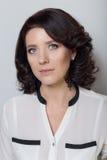 Η όμορφη κομψή γυναίκα καταδεικνύει την εφαρμογή του makeup σε ένα άσπρο υπόβαθρο στο στούντιο Στοκ Φωτογραφία