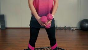 Η όμορφη κυρία κάνει την αθλητική άσκηση με τους αλτήρες στο τραμπολίνο στη γυμναστική φιλμ μικρού μήκους